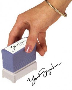 A hand holding a stamp that leaves your signature