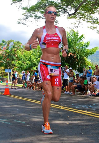 Image of Caroline Steffan wearing red sportswear and orange greeper laces, running outdoors in Kona