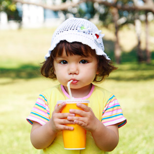 Image of a brown-haired toddler in a sunny garden, drinking from a cup using a straw