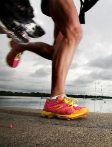 Image of a man running next to a lake with his dog, wearing brightly coloured trainers and greeper laces.