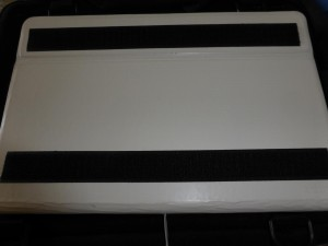 Photograph shows the back of a white tablet computer case, with two parallel strips of black adhesive hook tape on the back.