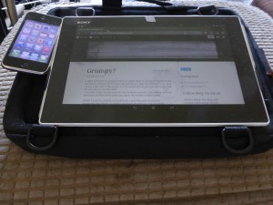 Photograph of a tablet computer and iPhone attached to the tray surface of the Trabasack Mini Connect wheelchair tray bag