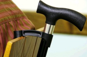 A Walking stick resting on the back of a chair being securely held by a crutch holder