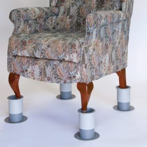Image is a photograph of a patterned, fabric armchair with leg raisers