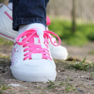 Image of a girls feet wearing white trainers with a floral motif and bright pink Greeper laces
