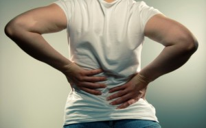 Image of a woman holding her back in pain