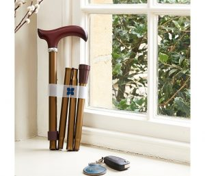 Image is a photograph of a bronze-coloured walking stick with wooden handle, folded neatly and placed upright on a windowsill next to a set of car keys