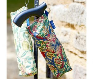 Image is a photograph of a folded walking stick inside a William Morris-inspired print, hanging against a sandstone wall