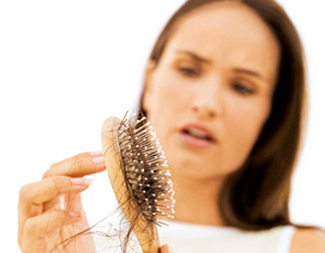 Image of a lady examining a hair brush with excess hair on it.