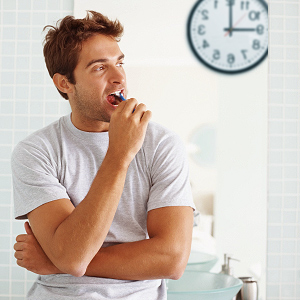 Image of a man brushing his teeth whilst looking at a clock behind him.