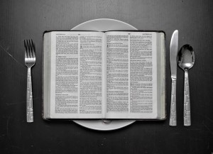 Black and white photograph of an open bible on an empty plate, with cutlery either side.