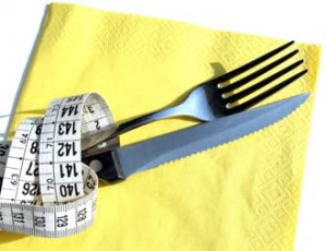 Image of a knife and fork wrapped in a tape measure upon a yellow napkin
