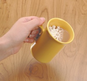 wheelchair drinking aid with ladies hand holding a yellow mug with tea and a Easi 2 Drink aid inside.