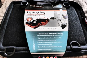 Photographic overview of the Trabasack Mini Connect in its packaging, which lists the benefits and features of the lap tray bag