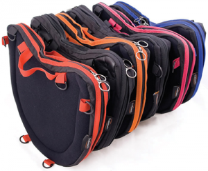 Image shows a photograph of Trabasack Curve bags in various trim colours, stood on end and lined-up one behind another