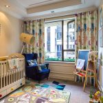 Image is a photograph of a child's nursery with cot, chair and drawing easel. At the window hangs animal patterned blackout curtains