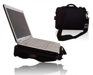 Image shows a photograph of the Trabasack Mini with a laptop on the tray surface