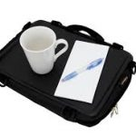 Image shows a photograph of the Trabasack Mini with a cup and pad and pen on the tray surface