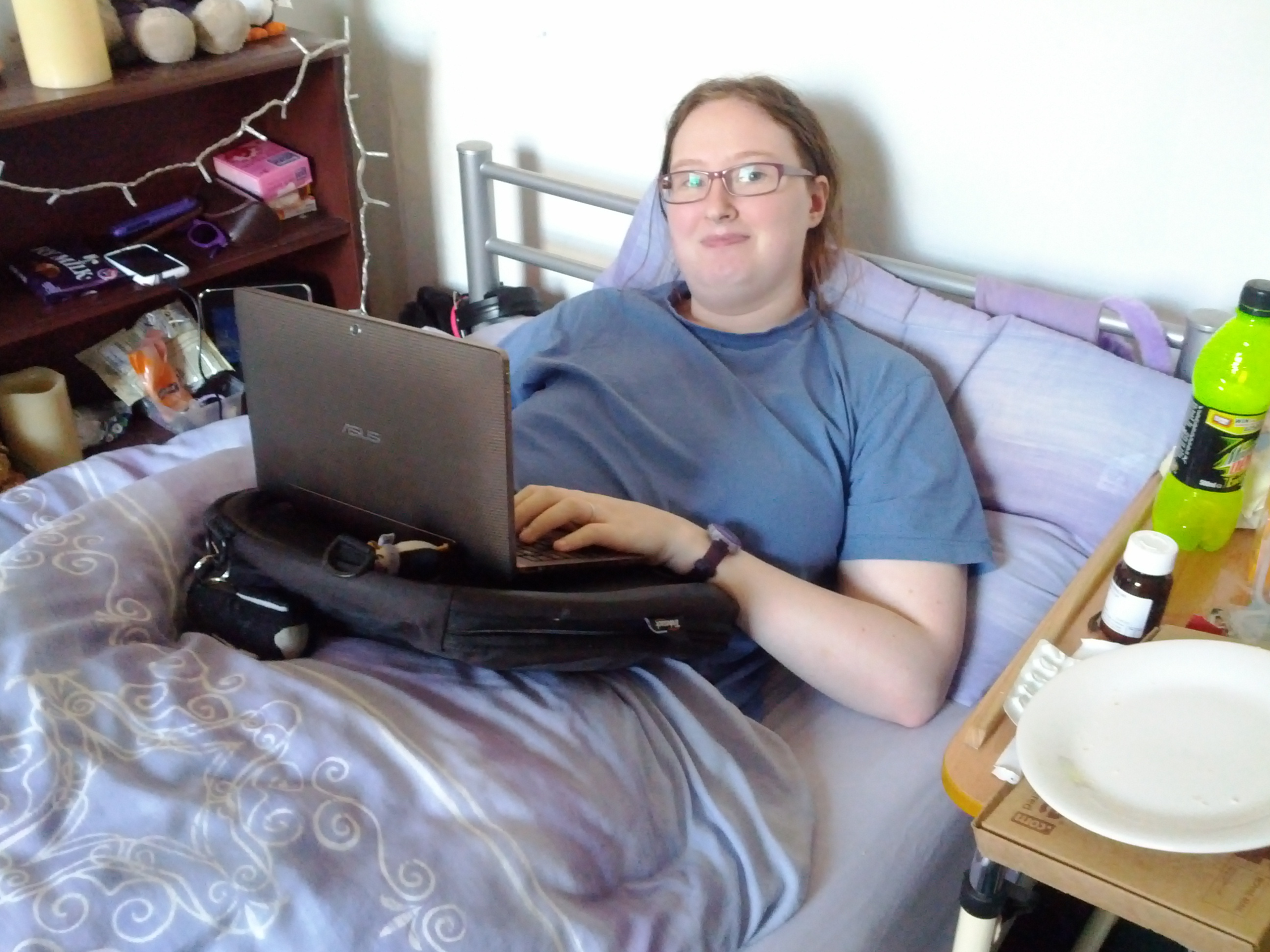 person in bed with a trabasack lap tray and a laptop on it