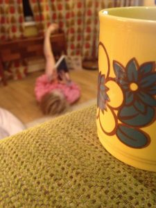 Image shows a photograph of a close-up of a tea cup, with a young girl out of focus in the background, lying on the floor reading a book