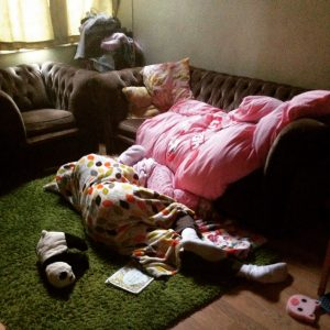 Image shows blankets and duvets strewn across a sofa and the floor, with a girl and her dad asleep on the floor