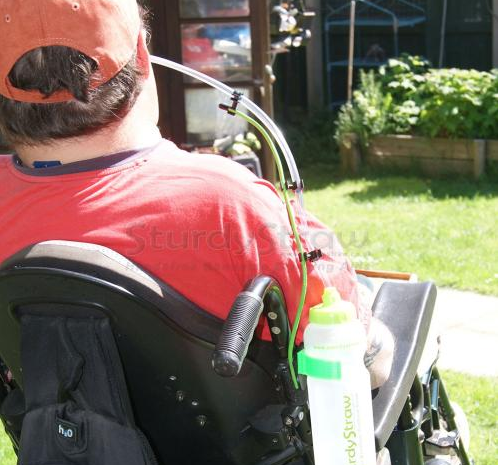 A man in a wheelchair showing a bottle with a plastic straw attached and the straw in a place he can reach it easily.