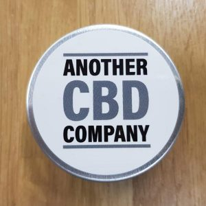 Image is a photograph of a small metal tin of CBD Joint balm on a wooden table