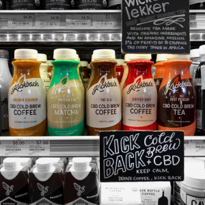 Image is a photograph of a shelf inside a fridge in a store in America, showing various CBD-infused beverages
